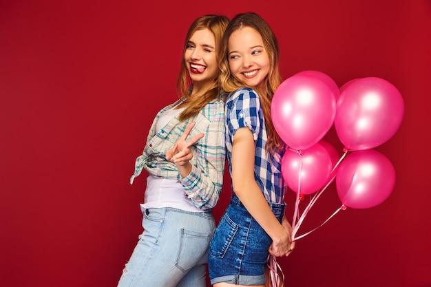 Mulheres posando com grande caixa de presente e balões rosa Foto gratuita