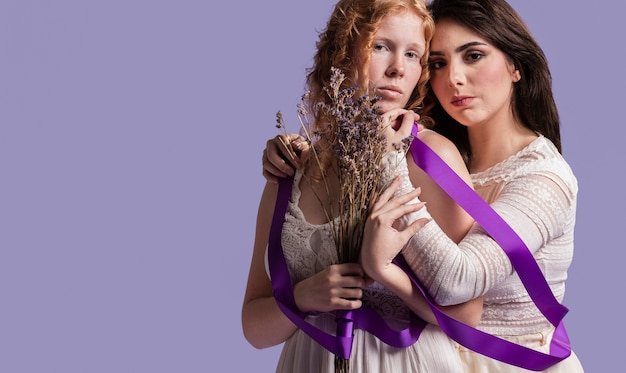 Mulheres posando com lavanda e fita enquanto abraçando com espaço de cópia Foto gratuita
