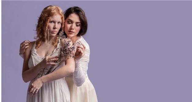 Mulheres posando com um buquê de lavanda enquanto abraça e copia o espaço Foto gratuita