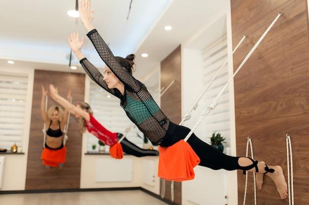 Mulheres praticando ioga em cordas, estendendo-se no ginásio. estilo de vida apto e bem-estar Foto Premium