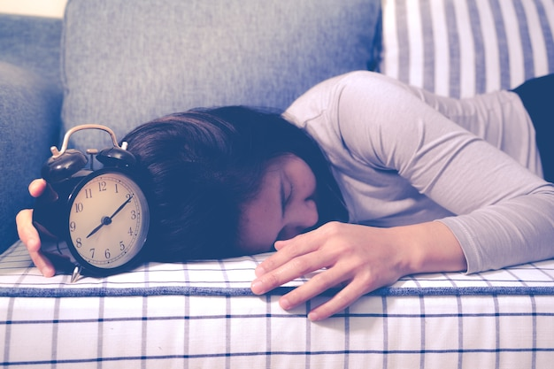 Mulheres preguiçosas que coloc no sofá após o alarme do pulso de disparo, conceito atrasado da excitação Foto Premium