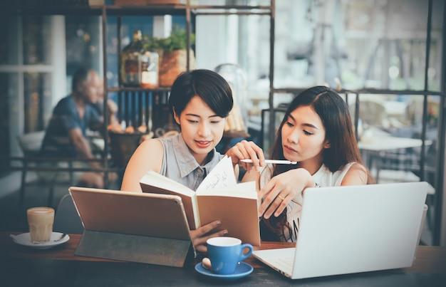 Mulheres que verific um caderno em um café Foto gratuita