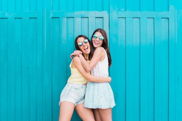 Mulheres, rir, e, abraçando, enquanto, ficar, ligado, rua Foto gratuita