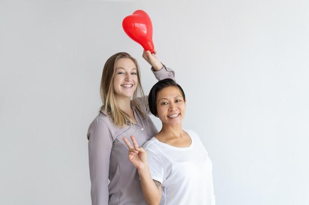 Mulheres, segurando, coração amoldou, balloon, e, mostrando, sinal vitória Foto gratuita