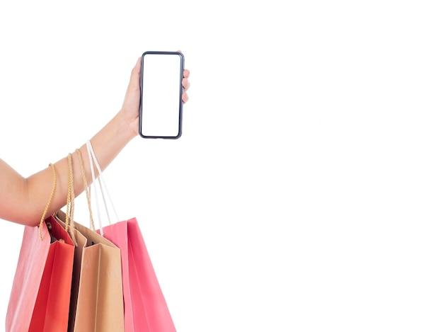Mulheres segurando smartphone com tela em branco e sacolas de compras na parede branca Foto Premium
