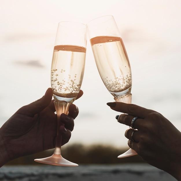 Mulheres segurando taças de champanhe no fundo por do sol Foto gratuita