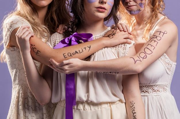 Mulheres segurando um ao outro enquanto pintado com palavras Foto gratuita