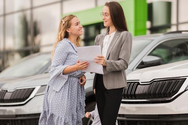 Mulheres segurando um contrato e olhando um ao outro Foto gratuita