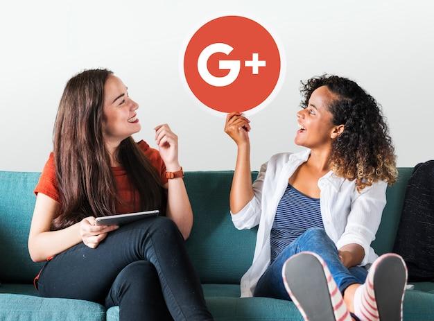 Mulheres segurando um ícone do google plus Foto gratuita