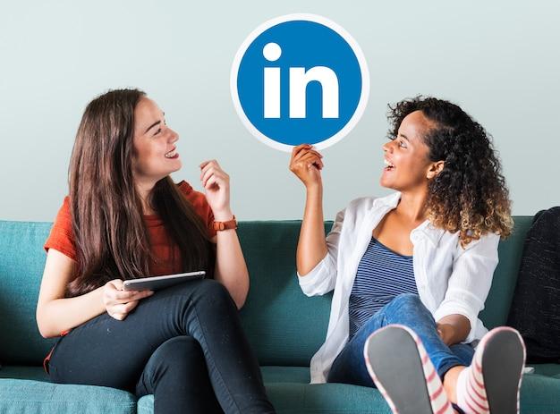 Mulheres segurando um logotipo do linkedin Foto gratuita