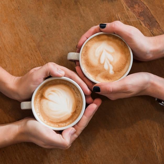 Mulheres, segurando, xícaras café, ligado, tabela madeira Foto gratuita