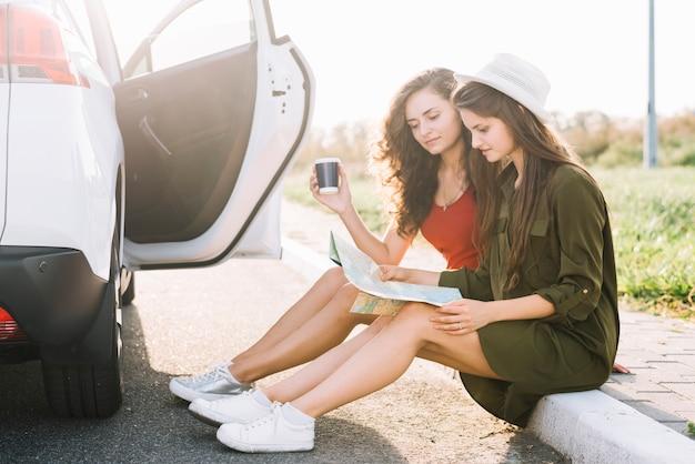 Mulheres, sentando, ligado, borda, com, mapa Foto gratuita