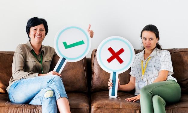 Mulheres, sentando, ligado, sofá, segurando, carrapato, ícones Foto Premium