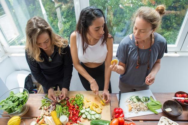 Mulheres sérias conversando e cortando legumes na cozinha Foto gratuita