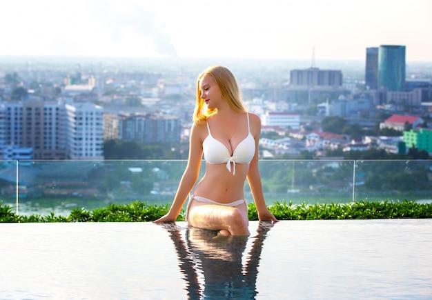 Mulheres sexy com biquíni branco, relaxar-se à beira da piscina Foto Premium