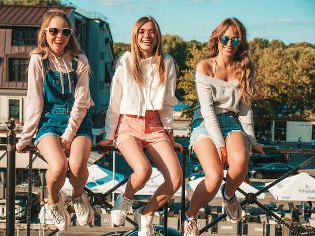 Mulheres sexy, sentado no corrimão na rua. modelos positivos se divertindo em óculos de sol. eles se comunicando e discutindo algo Foto gratuita
