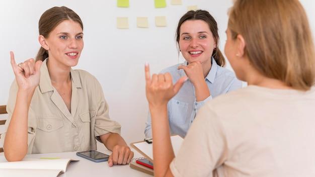 Mulheres sorridentes conversando à mesa usando linguagem de sinais Foto gratuita