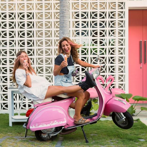 Mulheres sorridentes na scooter tomando sorvete Foto gratuita