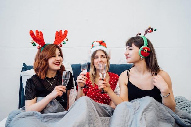Mulheres sorridentes segurando copos de vinho e curtindo a festa do pijama Foto gratuita