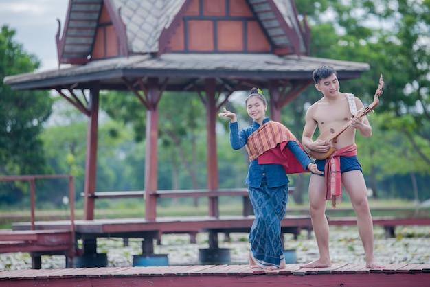 Mulheres tailandesas, e, homem, em, traje nacional, com, pino violão, (plucked, amarrado, instrumento) Foto gratuita