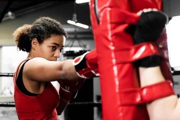 Mulheres treinando juntos no centro de boxe Foto gratuita