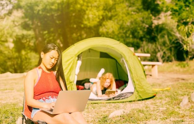 Mulheres, usando, gadgets, enquanto, acampamento Foto gratuita