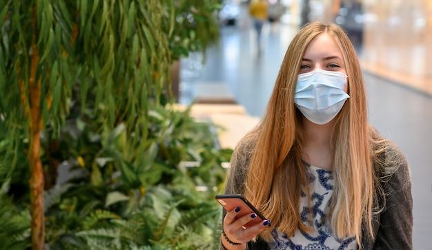 Mulheres usando máscaras sentadas no shopping, com telefone social espaçado. risos, sorrindo. Foto Premium
