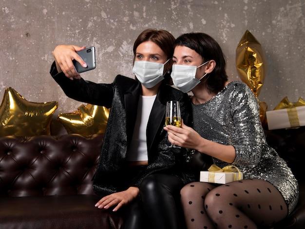 Mulheres usando máscaras tirando uma selfie Foto gratuita