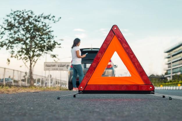 Mulheres usando telefone celular para tirar fotos de seu carro que abre o capô. Foto Premium