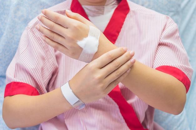 Mulheres vestindo pacientes vermelhos dor no pulso e uma bola de algodão nas costas da mão. Foto Premium