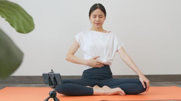 Mulheres vestindo roupas esportivas, treinamento online, curso de ioga em smartphone Foto Premium
