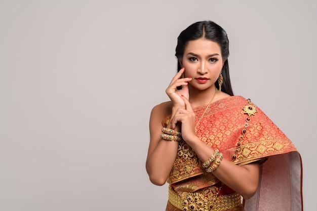 Mulheres vestindo roupas tailandesas e mãos tocando seus rostos Foto gratuita