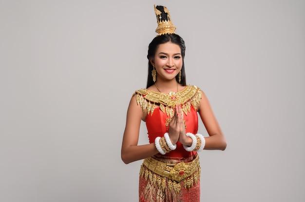 Mulheres vestindo roupas tailandesas que pagam respeito, símbolo sawasdee Foto gratuita