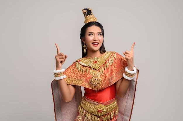 Mulheres vestindo trajes tailandeses que são simbólicos, apontando os dedos Foto gratuita