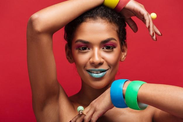 Multicolor jovem mulata com maquiagem moda olhando na câmera gesticulando mãos com pulseiras, parede vermelha Foto gratuita