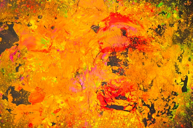 Multicolor pintado em pó na mesa preta Foto gratuita