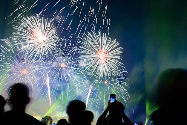 Multidão assistindo fogos de artifício e comemorando a cidade fundada. os fogos-de-artifício coloridos bonitos indicam no urbano para a celebração na noite escura. Foto Premium