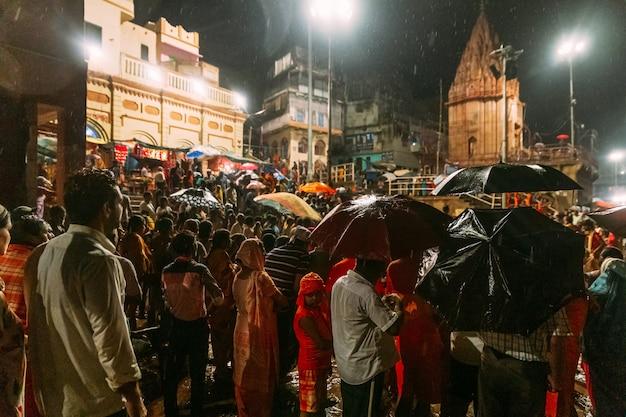 Multidão cheia de pessoas esperando por abençoar na chuva Foto Premium