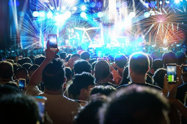 Multidão de concerto de música fanclub mão segurando o telefone inteligente móvel, tendo registro de vídeo ou transmissão ao vivo Foto Premium