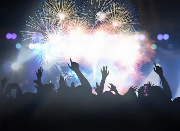 Multidão de concerto em silhuetas do clube de fãs de música com ação de mostrar a mão para celebrar com abeto Foto Premium