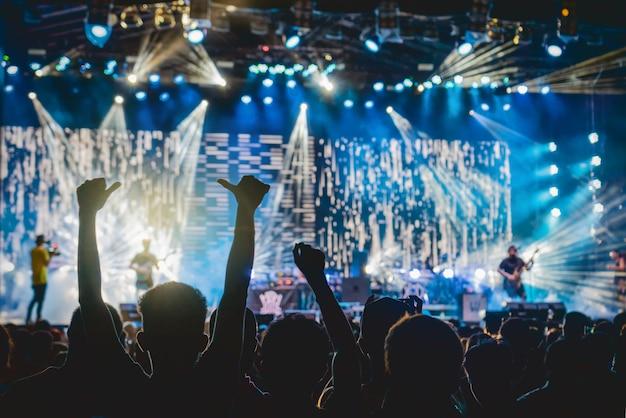 Multidão de concerto em silhuetas do fã-clube de música com ação de mão de mostrar que acompanham o cantor Foto Premium