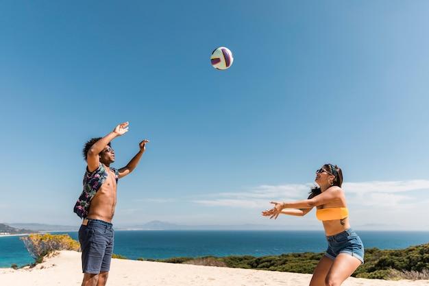 Multirraciais amigos jogando vôlei de praia Foto gratuita
