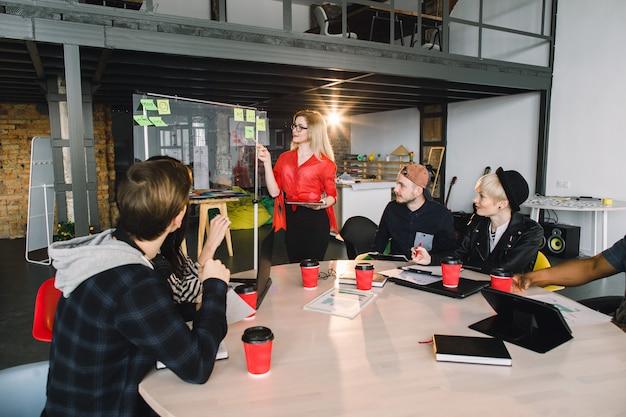 Multirraciais jovens criativos no escritório moderno. grupo de jovens empresários estão trabalhando em conjunto com laptop, tablet, telefone inteligente, notebook. equipe de sucesso hipster no coworking. freelancers. Foto Premium