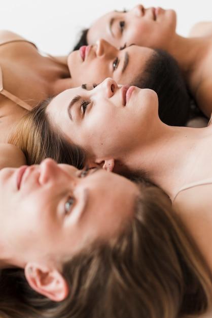 Multirraciais mulheres bonitas deitada juntos Foto gratuita
