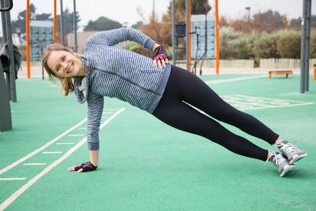 Músculos do núcleo de treinamento garota esportiva positiva Foto gratuita