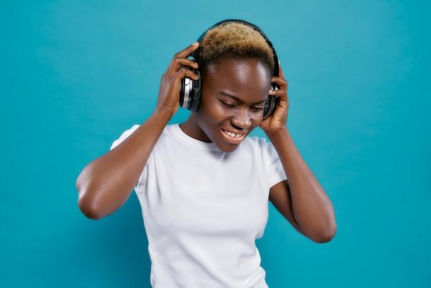 Música africana positiva mulher com fones de ouvido. Foto Premium