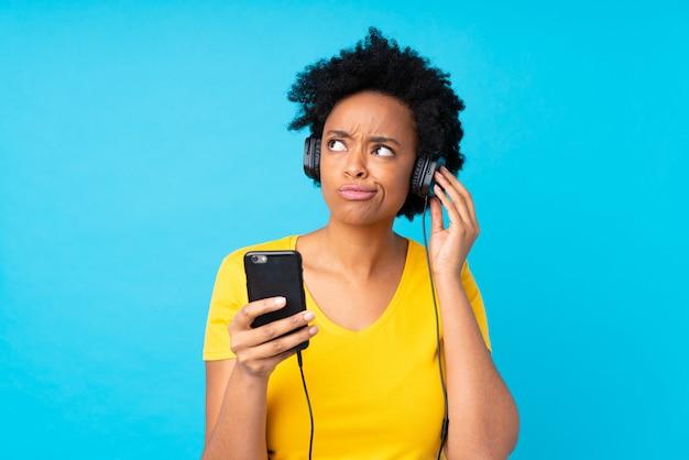 Música afro-americana jovem com um celular sobre parede azul isolada Foto Premium