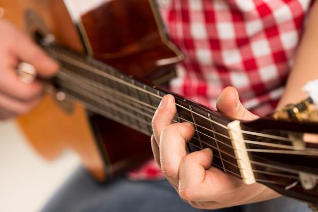 Música, close-up. músico segurando uma guitarra de madeira Foto gratuita