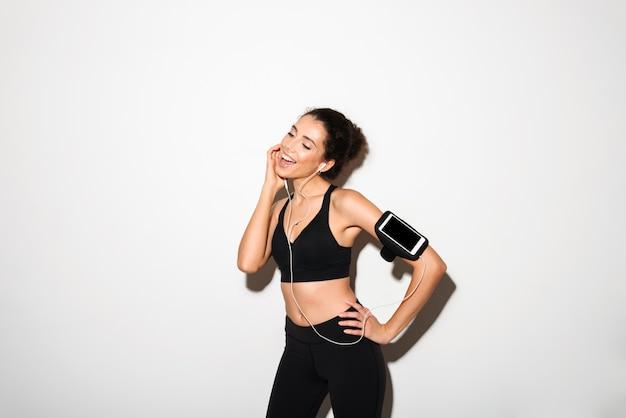 Música de mulher morena fitness encaracolado satisfeito pelo smartphone Foto gratuita