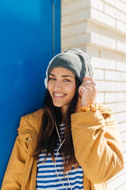 Música de mulher sorridente, olhando para a câmera Foto gratuita